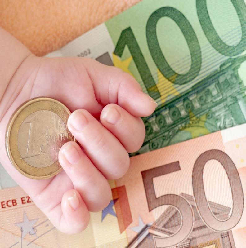 Mano bimbo con euro sopra banconote per bonus bebè