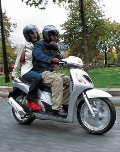 Conducente e passeggero in coppia su uno scooter